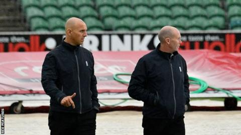 Umpires Alex Wharf and Mike Burns out on the field for an inspection during a rain break in the County season