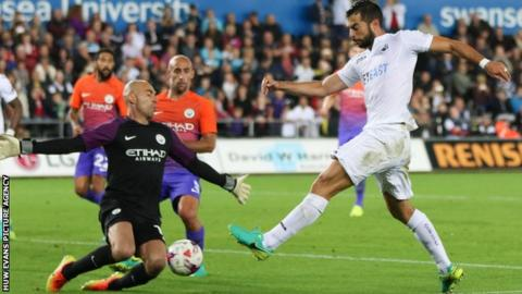 Jordi Amat is challenged by Manchester City goalkeeper Willy Caballero