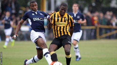 Christian Mbulu tackles Folkestone Invicta's Ade Yussuf while playing for a Millwall XI