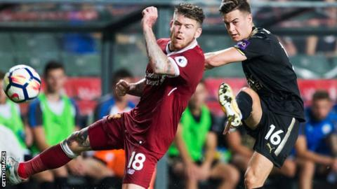 Liverpool's Alberto Moreno (L) and Leicester City's Tom Lawrence (R) compete for the ball during the final of the Premier League Asia Trophy