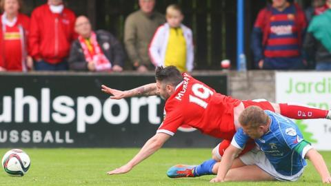 Cliftonville's Ciaran Murray goes down as David Armstrong of Dungannon Swifts challenges at Stangmore Park
