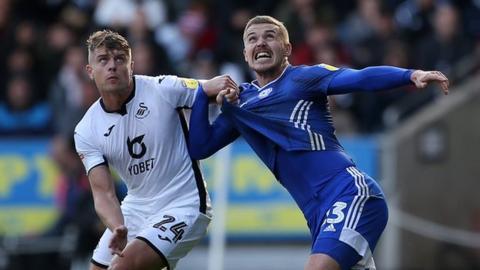 Swansea City's Jake Bidwell (L) and Cardiff City's Danny Ward