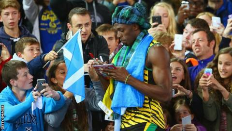 Usain Bolt of Jamaica signs autographs after winning gold in the 4x100m relay at Glasgow 2014