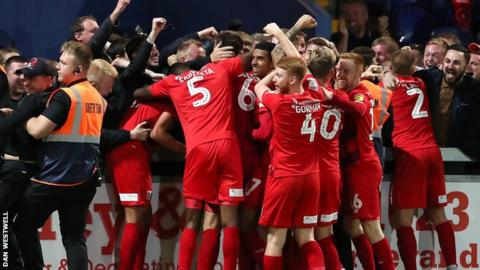 Leyton Orient players and interim head coach Ross Embleton celebrate their late winner with the travelling fans