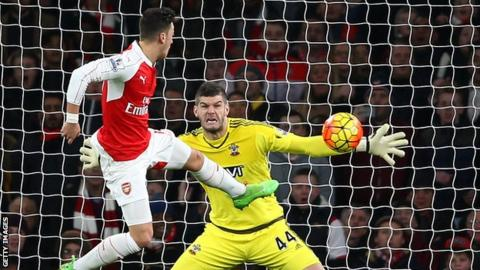 Fraser Forster saves a shot from Mesut Ozil
