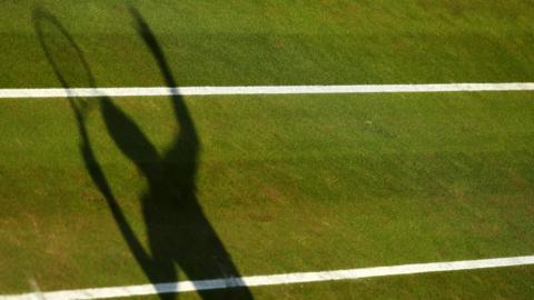 A shadow of a tennis player serving on a grass court
