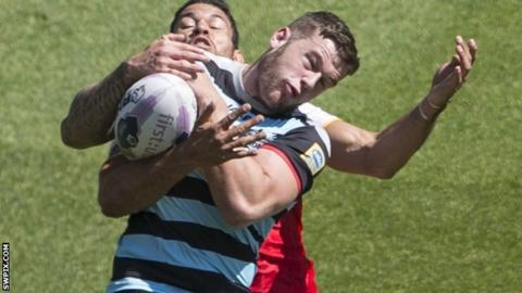 Thomas Minns competes for the ball against Catalans winger Daryl Millard
