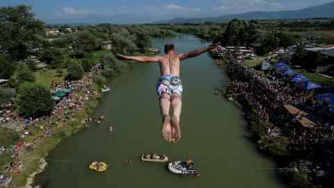 TOPSHOT - People look at a man as he jumps from the 22 meters high bridge 'Ura e Shenjte' during the annual traditional High Diving competition near the town of Gjakova on July 22, 2018. (Photo by Armend NIMANI / AFP) (Photo credit should read ARMEND NIMANI/AFP/Getty Images)