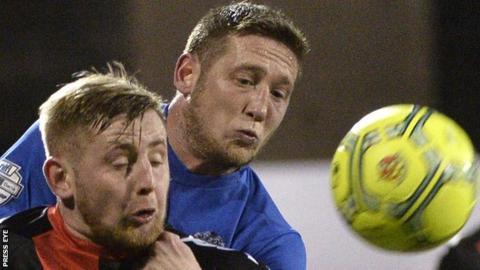David Cushley of Crusaders in action against Glenavon defender Kris Lindsay