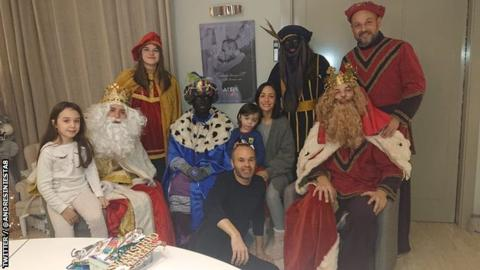 A photo of former Barcelona midfielder Andres Iniesta (centre) surrounded by his family and a group of people dressed in costumes to mark Three Kings Day, two of whom are in black makeup