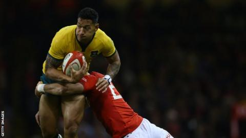 Israel Folau is tackled by a Wales player