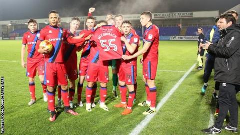Rochdale players hold a shirt in support of ill five-year-old Joshua McCormack