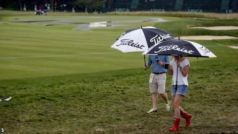 Fans on the Oakmont course shelter from the rain