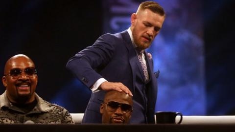 Conor McGregor puts his hand on Floyd Mayweather's head
