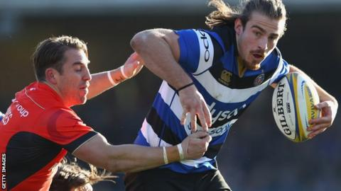 Max Clark of Bath is challenged by Chris Wyles of Saracens