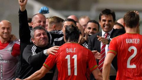 Gareth Bale celebrates with Wales' coaches