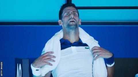 Novak Djokovic takes a break with an ice towel around his neck