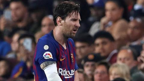 Lionel Messi walks off the field holding his right arm
