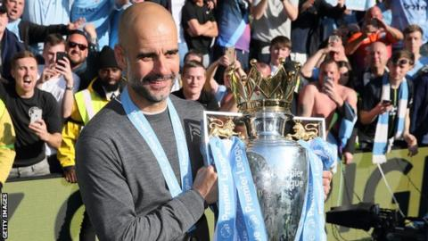 Manchester City boss Pep Guardiola poses with the Premier League trophy after winning the title