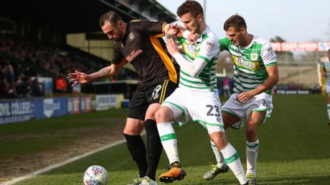 paul hayes shields the ball from two yeovil defenders