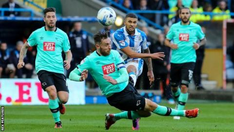 Richard Keogh tries to block a shot from Huddersfield's Nakhi Wells