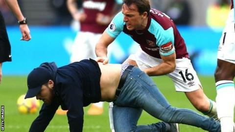 West Ham skipper Mark Noble drags a pitch invader to the floor