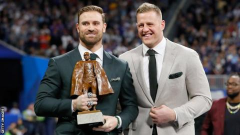 Chris Long holds the Walter Payton Award next to JJ Watt during Super Bowl 53