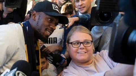 Bolt poses for photographs with the fans at Sydney airport before his stint with Central Coast Mariners