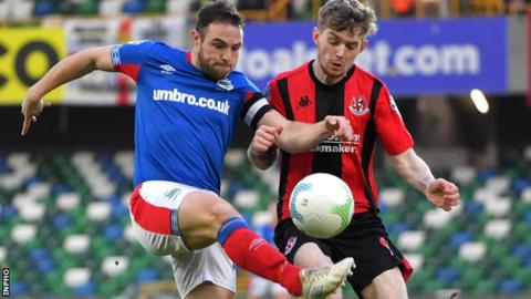 Linfield midfielder Jamie Mulgrew battles with Crues forward Jamie McGonigle for the ball