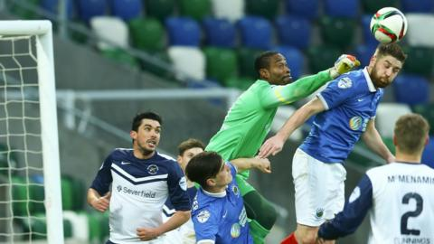 Ballinamallard United keeper Alvin Rouse is beaten to the high ball by Linfield defender Mark Stafford at Windsor Park
