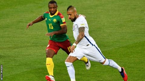 Cameroon's Sebastian Siani (left) battles for the ball with Chile's Arturo Vidal