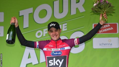 Team Sky's Pavel Sivakov holds up champagne and flowers on the podium after winning stage two of the Tour of the Alps
