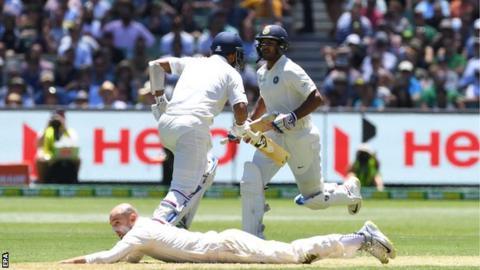 India's Cheteshwar Pujara and Mayank Agarwal run as Nathan Lyon fields