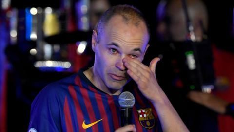 Andres Iniesta wipes away a tear as he addresses the Barcelona fans