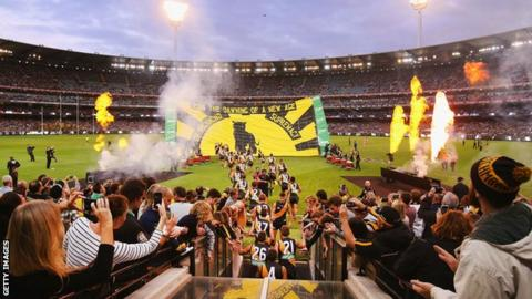 Fans cheer on Richmond players as they run onto the field at the MCG before their game against Carlton in 2019