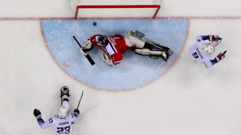 Rico Roman of United States is scoring a goal over Martin Kudela, goaltender of Czech Republic