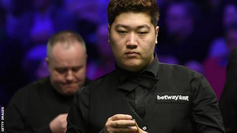 Yan Bingtao chalks his cue