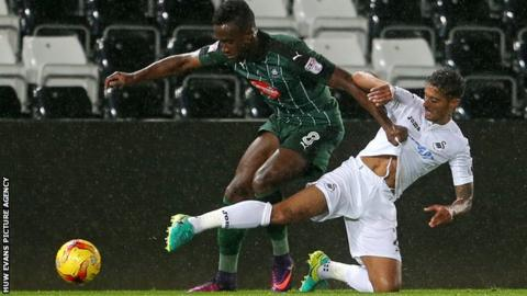 Jordan Slew of Plymouth Argyle is tackled by Kyle Naughton