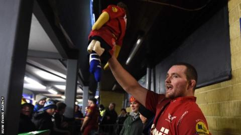 Scarlets captain Ken Owens holds aloft the Rag Doll Scarlets and Bath have competed for since 1921