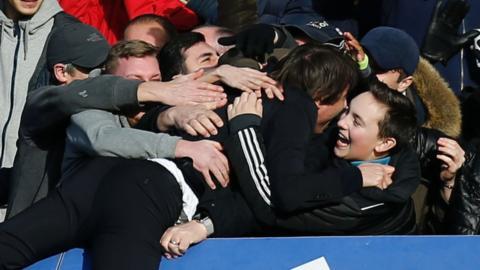 Antonio Conte jumps into the crowd at Stamford Bridge