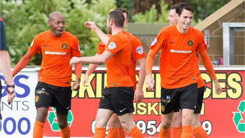 Carrick Rangers players congratulate Miguel Chines after the striker scored his goal in a 3-1 victory over Ballinamallard United