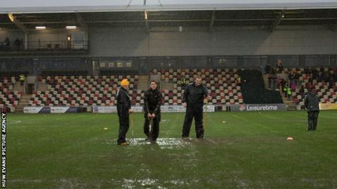 Ground staff work on the Rodney Parade pitch