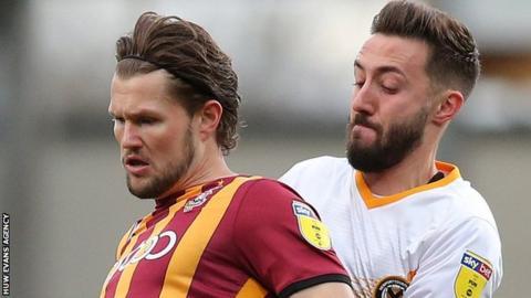 Bradford City's Jake Reeves holds off Josh Sheehan of Newport County