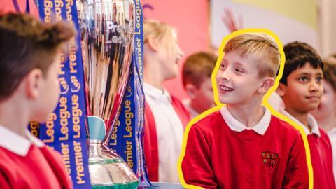 Young boys surrounding the Premier League trophy.