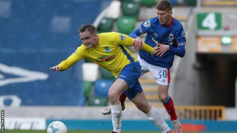 Northern Ireland Ballymena defender Andrew Burns is challenged by Linfield's Charlie Allen