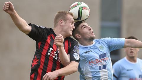 Crusaders striker Jordan Owens goes head to head with Ballymena United defender Michael Ruddy