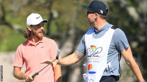 Tommy Fleetwood chats to his caddie Ian Finnis as he walks off the 12th green at Bay Hill