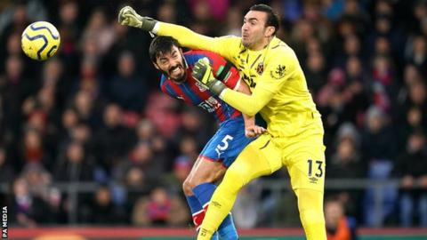Roberto punches the ball away from a Crystal Palace player in a Premier League match