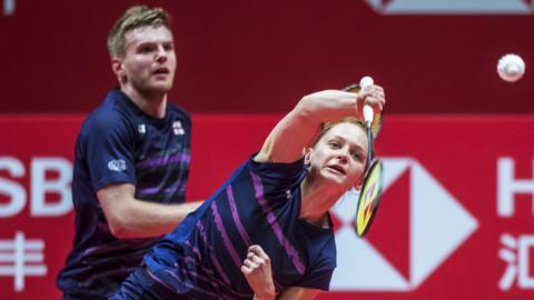 England's Lauren Smith plays a shot while mixed doubles partner Marcus Ellis looks on behind during the Badminton World Tour Finals in China