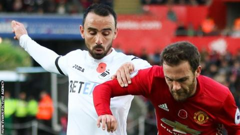 Leon Britton of Swansea City challenges Manchester United's Juan Mata